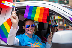 A feminine-presenting person waves a rainbow flag from a car window