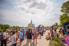 A mass of people walk toward the CMHR building in the Pride Parade