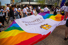 The University of Manitoba Pride flag is unfurled in a crowd