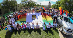 University of Manitoba Pride participants gather around the UM Queer flag