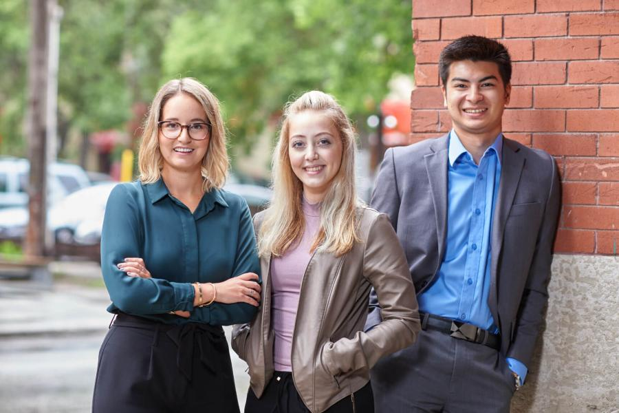 Three Asper School of Business students stand together smiling.