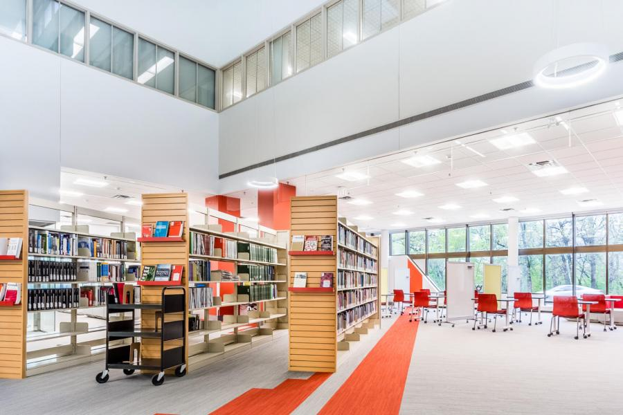 A bright open interior space of the Albert D. Cohen Management library with rows of books, and a seating area.