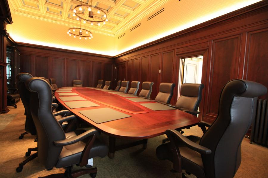 A large boardroom with a long  oval shaped table lined with black office chairs.