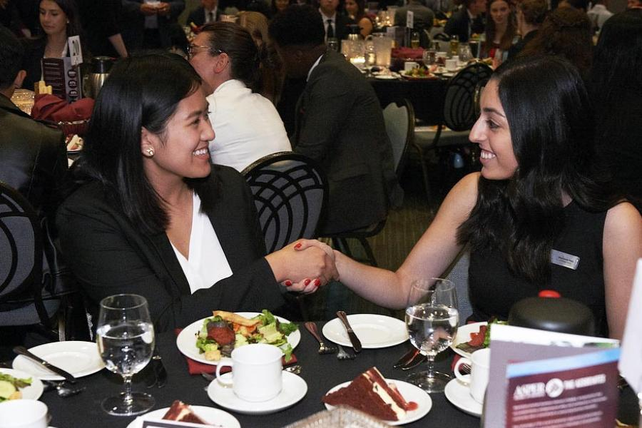 Two women shaking hands and smiling at a dinner table.