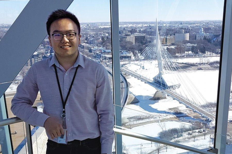A student stands at an upper window of the Canadian Museum of Human Rights, the Winnipeg skyline behind him.