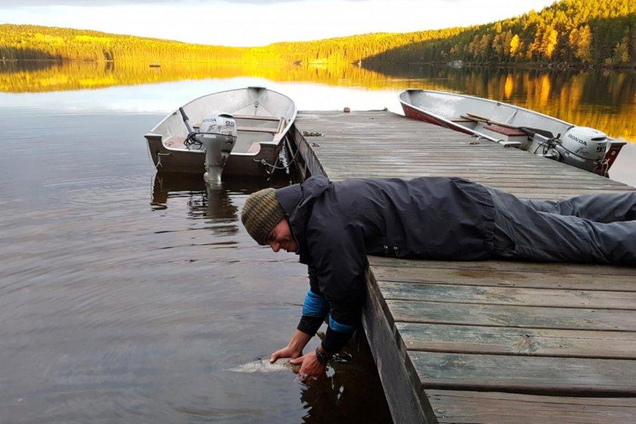 A young man in waterproof clothing lies on his stomach on a dock. He holds a fish in the water, set to release it.