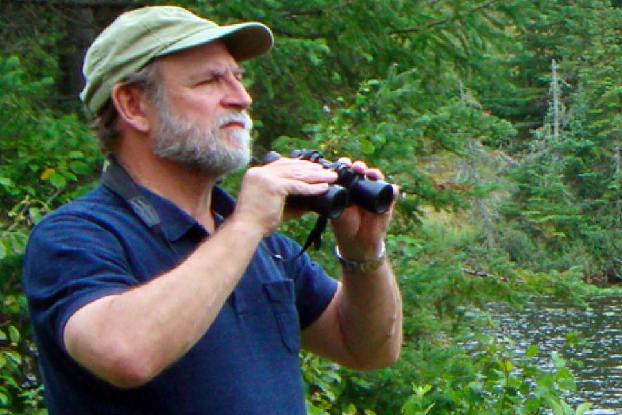 Zoologist Bill Watkins stands outdoors holding a pair of binoculars gazing out at a forested area.