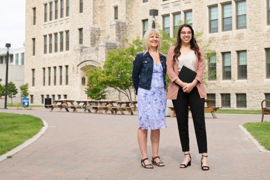 Career mentor Angelal stands with an international student outdoors in front of the Buller Biological building.