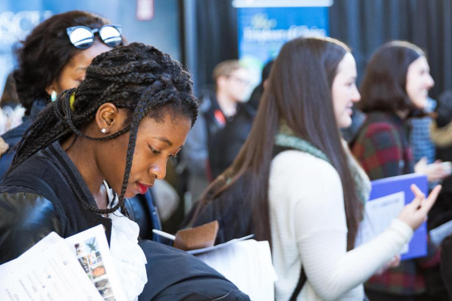 Students gathered at the annual career fair. A woman in the foreground reviews printed information she is holding.