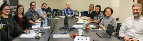Students and faculty in the Archival Studies program, 2019-2020, sitting around a seminar table.