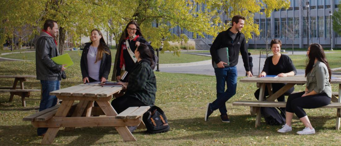 Group of University of Manitoba students sitting around picnic tables.