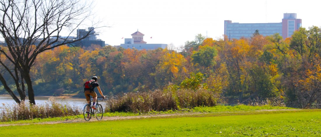 A person biking to the University of Manitoba on a scenic bike path along the Red River.