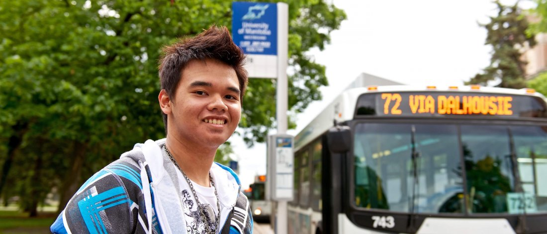 A University of Manitoba student waits at the bus stop for a bus.