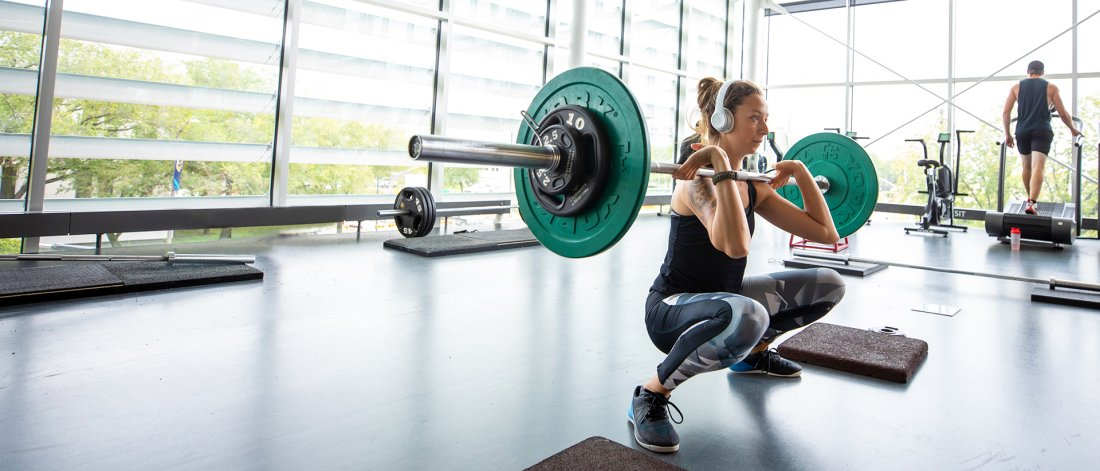 a person doing a barbell front squat at the active living centre