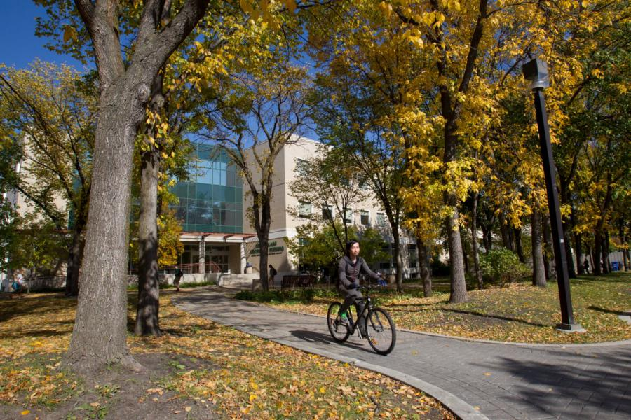 A University of Manitoba student on a bicycle outside the Helen Glass Centre of Nursing on a sunny autumn day