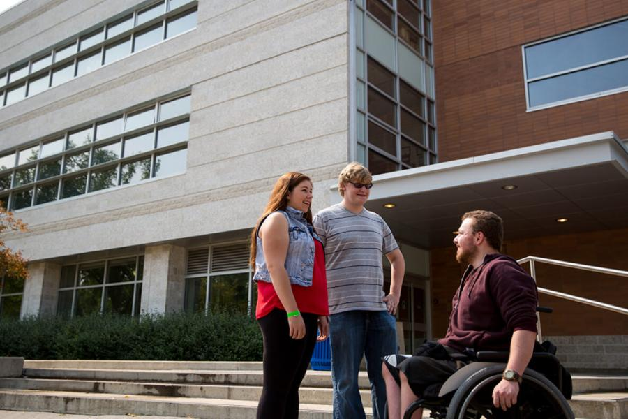 Two people standing talking to a third person in a wheelchair outside of a building at University of Manitoba