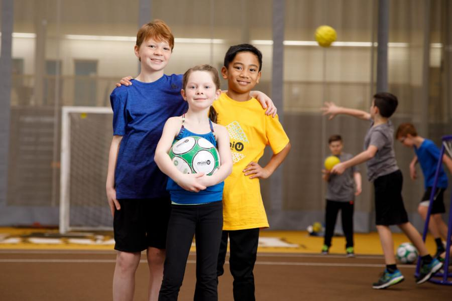 Three kids holding a soccer ball during the Mini U program
