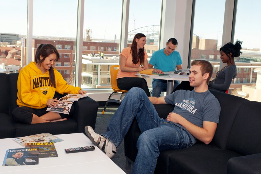 Several students reading, watching television and studying in a residence lounge room.