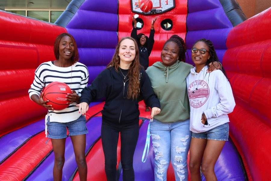 Five student residents play basketball in a bouncy castle.