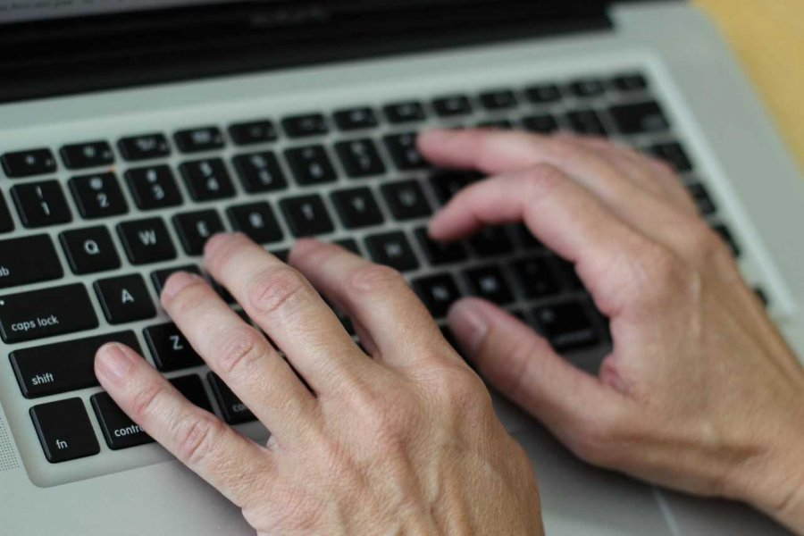 Hands on a laptop keyboard.