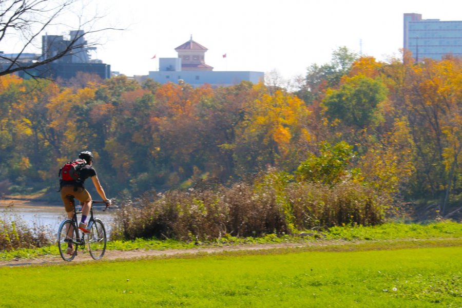 A University of Manitoba student biking to campus on a scenic bike path along the Red River.