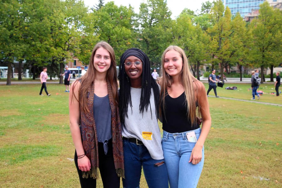 Three students stand beside each other and smile for the camera while standing in the Fort Garry campus Duckworth Quadrangle.