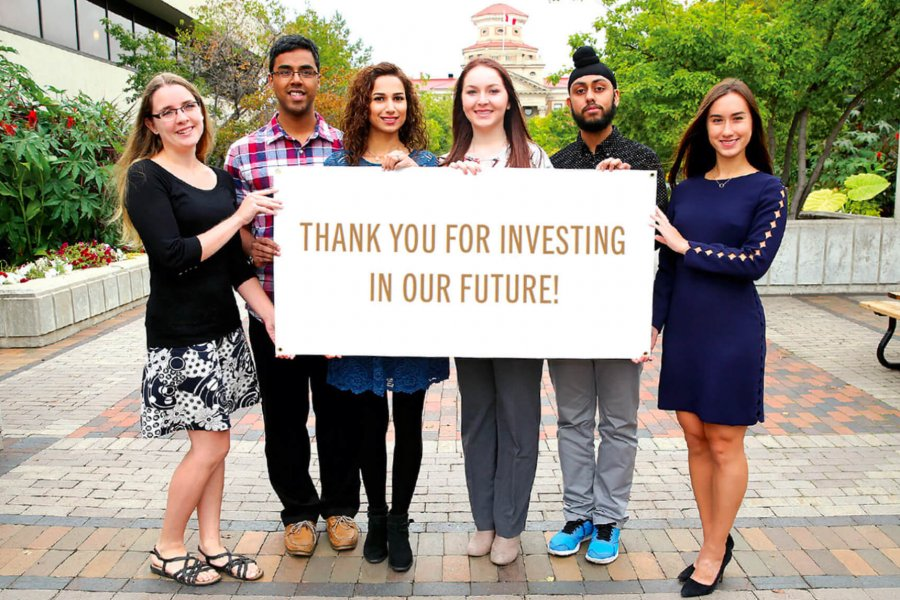 Six students stand together holding a sign thanking donors.