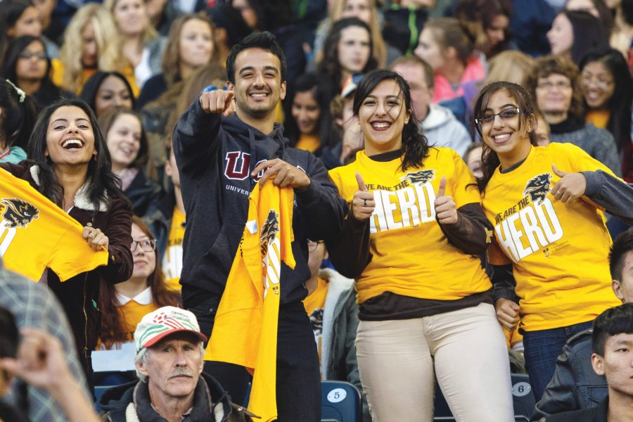 Students cheer on the Bisons during a football game at Investors Group Field.