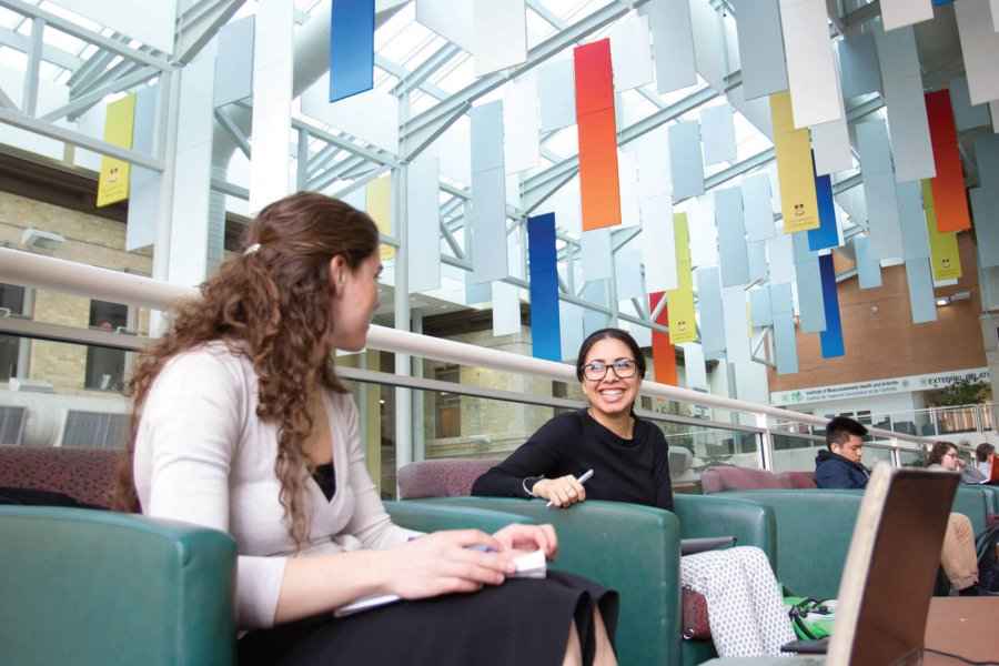 Two students sitting together in the University of Manitoba Bannatyne campus Buhler atrium.