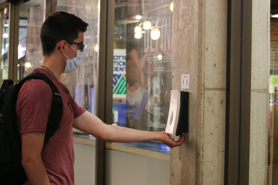 Student using hand sanitizer station on campus.