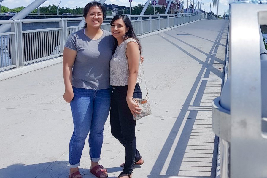Peer Mentor, Muntaha, stands with her pair, Angelica, on the Esplanade Riel Bridge at the Forks in Winnipeg.